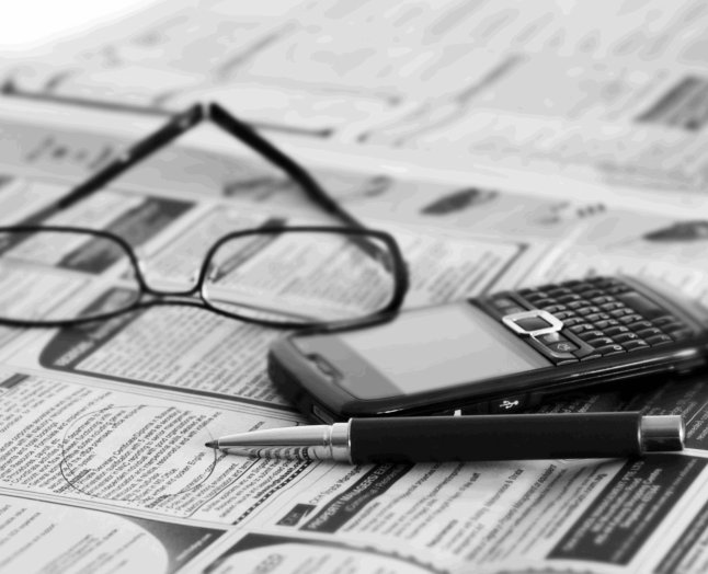 pen,cellphone and eyeglasses over the newspaper